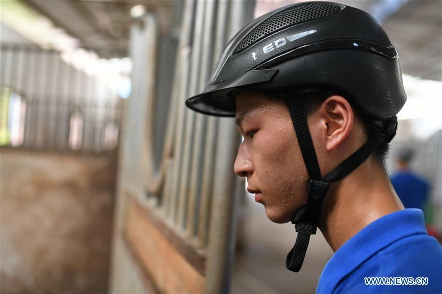 Huang Wanpeng, a student of Sunshine Riding School, works at the school stable in Yihuang County of Fuzhou, east China\'s Jiangxi Province, July 25, 2018. Equestrianism had never been heard of in Yihuang, an agricultural county in east China\'s Jiangxi Province, until Sunshine Riding School began recruiting rural teenagers in 2015. So far, most of the 90 students are working or aspiring to work in horse riding clubs in China\'s largest cities such as Beijing, Shanghai and Hangzhou. (Xinhua/Zhou Mi)