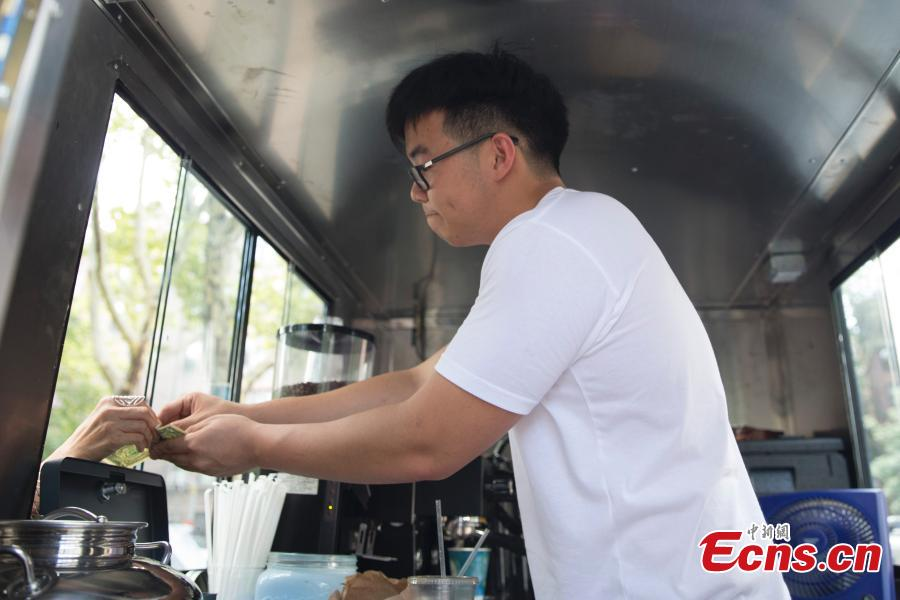 Food truck owner Fei Xiang exchanges free coffee for ten cigarette butts, picked up by customers in Flushing, New York City, U.S., July 26, 2018. Fei's food truck offered customers free coffee in exchange for ten cigarette butts, picked up from around the community, as an initiative to improve the local environment. Fei said he delivered about five to ten cups of free coffee a day. (Photo: China News Service/Liao Pan)