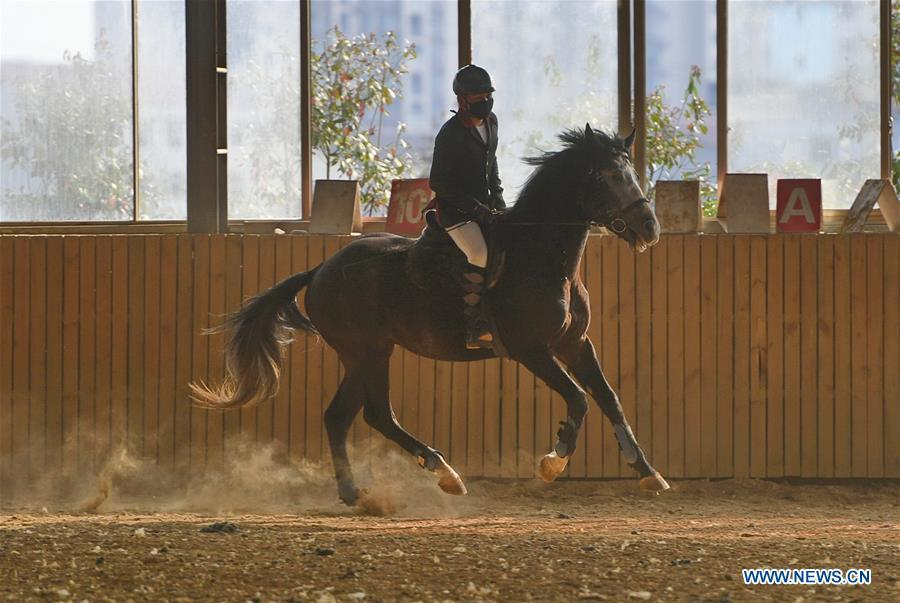 A student attends a training session at Sunshine Riding School in Yihuang County of Fuzhou, east China\'s Jiangxi Province, March 13, 2018. Equestrianism had never been heard of in Yihuang, an agricultural county in east China\'s Jiangxi Province, until Sunshine Riding School began recruiting rural teenagers in 2015. So far, most of the 90 students are working or aspiring to work in horse riding clubs in China\'s largest cities such as Beijing, Shanghai and Hangzhou. (Xinhua/Zhou Mi)
