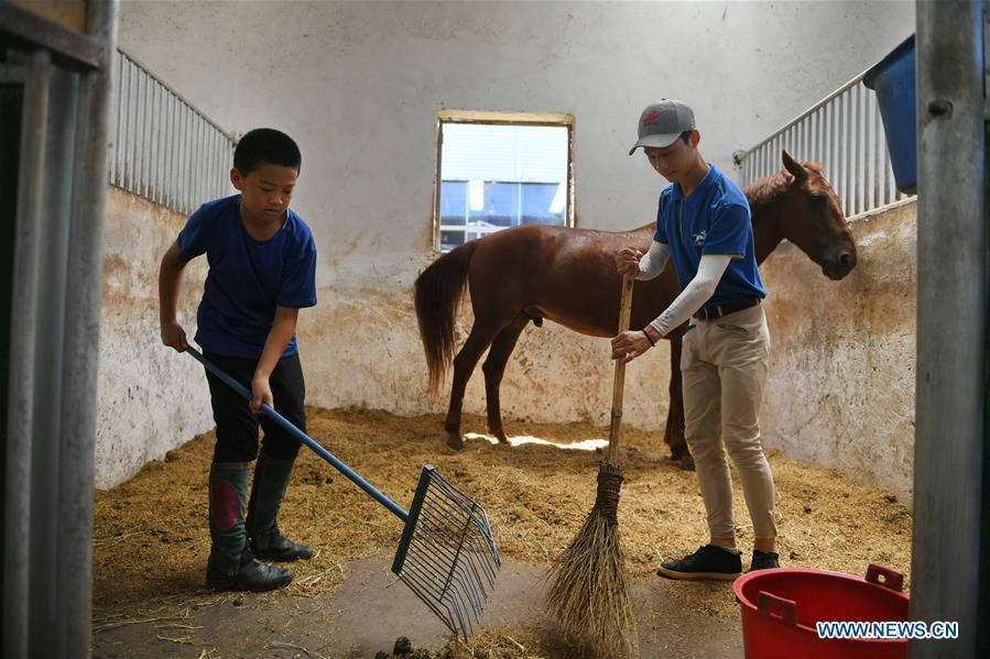 Huang Wanpeng (R), a student of Sunshine Riding School, cleans up the school stable together with one of his juniors in Yihuang County of Fuzhou, east China\'s Jiangxi Province, July 25, 2018. Equestrianism had never been heard of in Yihuang, an agricultural county in east China\'s Jiangxi Province, until Sunshine Riding School began recruiting rural teenagers in 2015. So far, most of the 90 students are working or aspiring to work in horse riding clubs in China\'s largest cities such as Beijing, Shanghai and Hangzhou. (Xinhua/Zhou Mi)