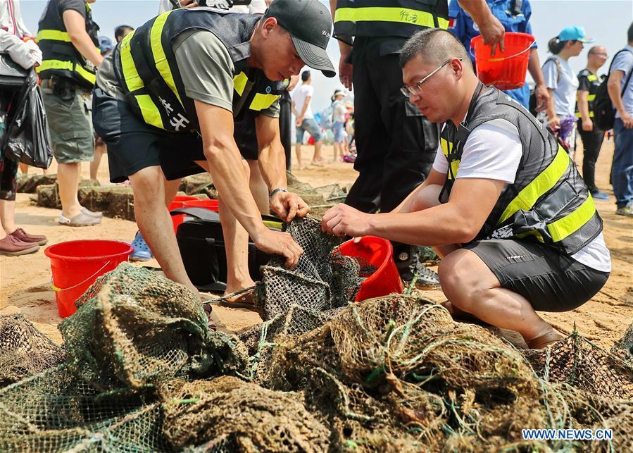 Volunteers clean up trash on a beach during an event calling for attention to marine ecology protection at the Golden Dream Bay in Qinhuangdao, north China\'s Hebei Province, July 27, 2018. (Xinhua/Cao Jianxiong)