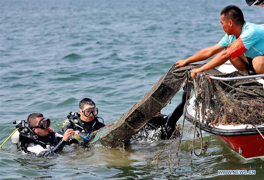 Volunteers clean up marine trash during an event calling for attention to marine ecology protection at the Golden Dream Bay in Qinhuangdao, north China\'s Hebei Province, July 27, 2018. (Xinhua/Cao Jianxiong)