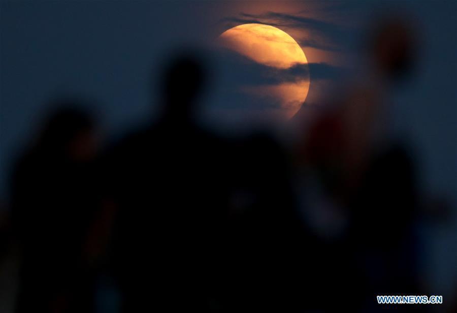 People watch the longest total lunar eclipse of the century at Jarun Lake in Zagreb, capital of Croatia, on July 27, 2018. (Xinhua/Igor Kralj)