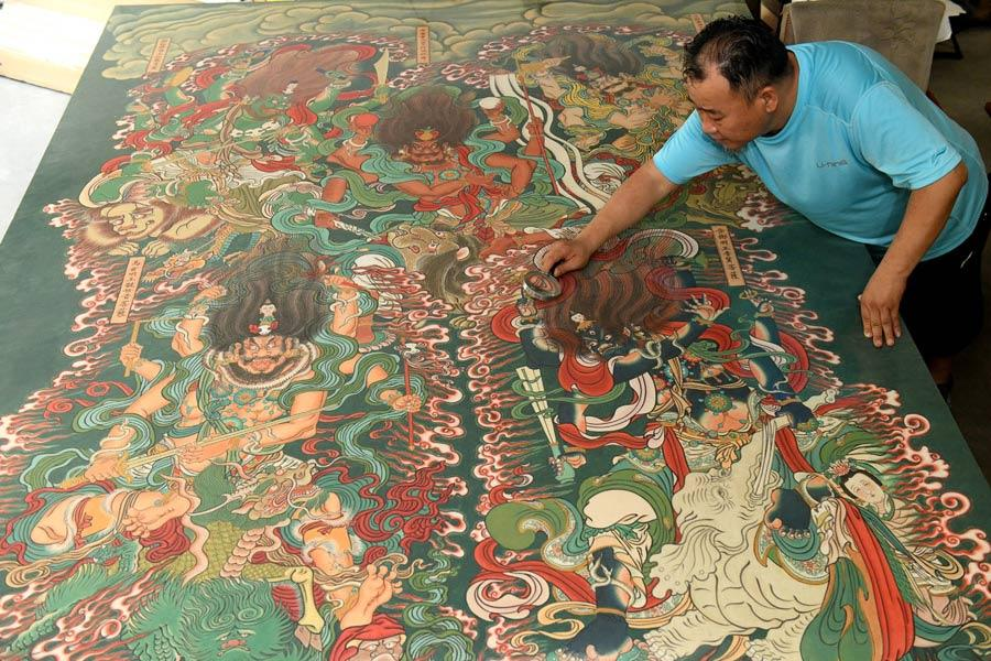 Yao Shulong checks his replica paintings of murals in Pilu Temple in his studio on July 24, 2018. (Photo/Xinhua)