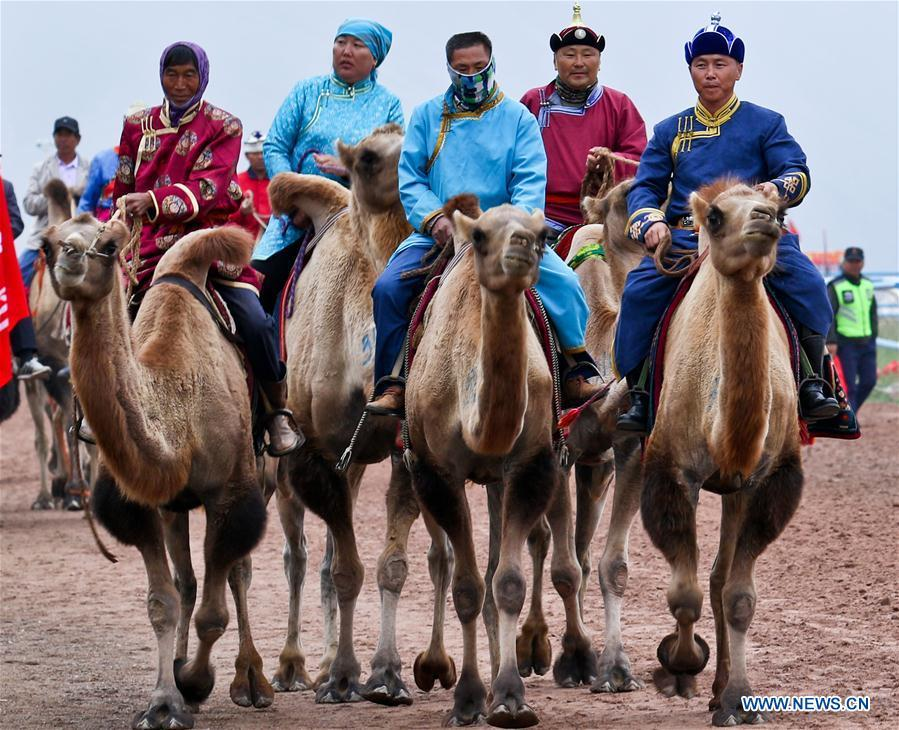 People are to take part in a camel racing during a traditional ethnic minorities sports meeting held at a racecourse in Sunan Yugur Autonomous County, northwest China\'s Gansu Province, July 28, 2018. (Xinhua/Wang Jiang)