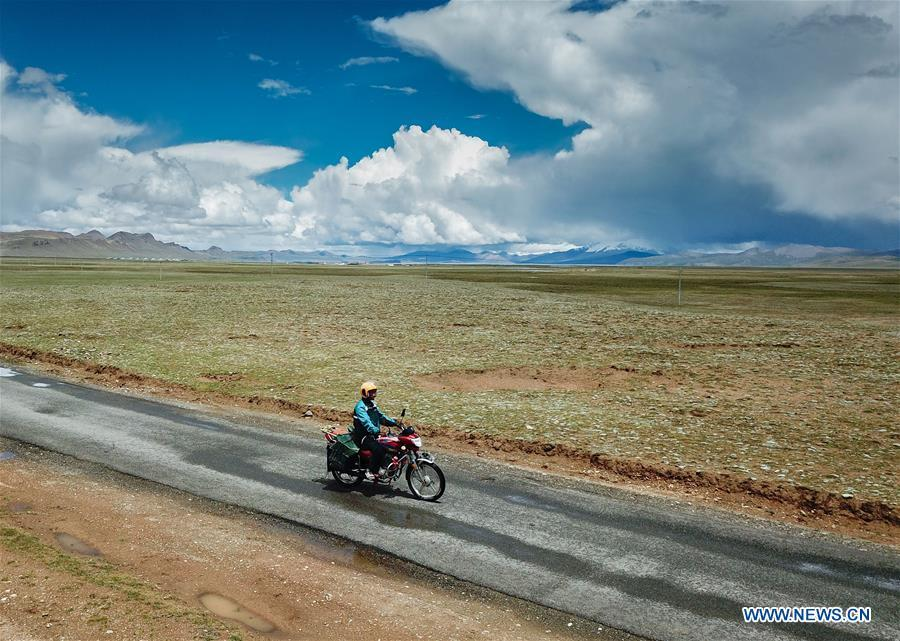 Motorbike courier Gesang Cering performs a mail delivery task in Pumaqangtang Township of Nagarze County in Shannan, southwest China\'s Tibet Autonomous Region, July 27, 2018. In Pumaqantang Township, the highest township in China, working as a postal service staff means delivering mails to addresses at altitudes of 5,000 meters and above. Gesang Cering, 29, is a motorbike courier with the local township branch of China Post. Twice a week, Gesang calls on the plateau villages under the township on a 160-km route, coping with extreme oxygen and temperature conditions. Despite its harsh geography, Tibet Autonomous Region has substantially improved the local postal service over the four decades since China\'s reform and opening up. By the end of 2017, the postal road network had managed to cover all towns and counties within the autonomous region. (Xinhua/Li He)