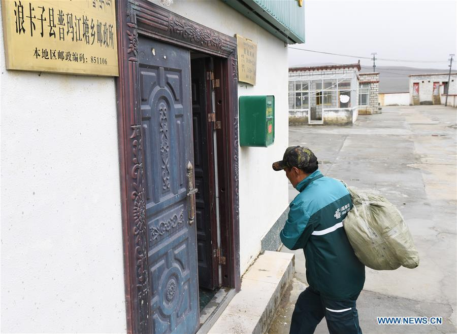 Postal courier Cering Quba carries a bag of mails to the township branch of China Post in Pumaqangtang Township of Nagarze County in Shannan, southwest China\'s Tibet Autonomous Region, July 23, 2018. In Pumaqantang Township, the highest township in China, working as a postal service staff means delivering mails to addresses at altitudes of 5,000 meters and above. Gesang Cering, 29, is a motorbike courier with the local township branch of China Post. Twice a week, Gesang calls on the plateau villages under the township on a 160-km route, coping with extreme oxygen and temperature conditions. Despite its harsh geography, Tibet Autonomous Region has substantially improved the local postal service over the four decades since China\'s reform and opening up. By the end of 2017, the postal road network had managed to cover all towns and counties within the autonomous region. (Xinhua/Li He)