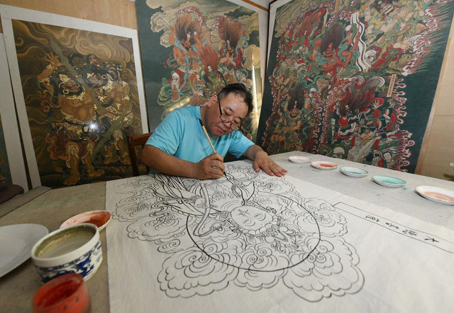 Yao Shulong creates replicas of traditional Chinese New Year paintings of Pilu Temple in his studio on July 24, 2018. (Photo/Xinhua)