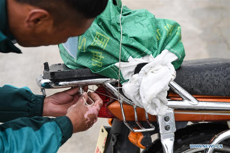 Motorbike courier Gesang Cering fixes a postal mail bag to the rear of his motorbike before setting off for work in Pumaqangtang Township of Nagarze County in Shannan, southwest China\'s Tibet Autonomous Region, July 23, 2018. In Pumaqantang Township, the highest township in China, working as a postal service staff means delivering mails to addresses at altitudes of 5,000 meters and above. Gesang Cering, 29, is a motorbike courier with the local township branch of China Post. Twice a week, Gesang calls on the plateau villages under the township on a 160-km route, coping with extreme oxygen and temperature conditions. Despite its harsh geography, Tibet Autonomous Region has substantially improved the local postal service over the four decades since China\'s reform and opening up. By the end of 2017, the postal road network had managed to cover all towns and counties within the autonomous region. (Xinhua/Li He)