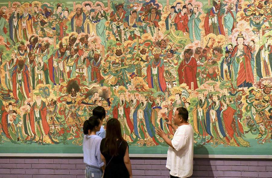 Yao Shulong introduces visitors at the Hebei Museum to the murals of Pilu Temple through his replica works on July 25, 2018. (Photo/Xinhua)