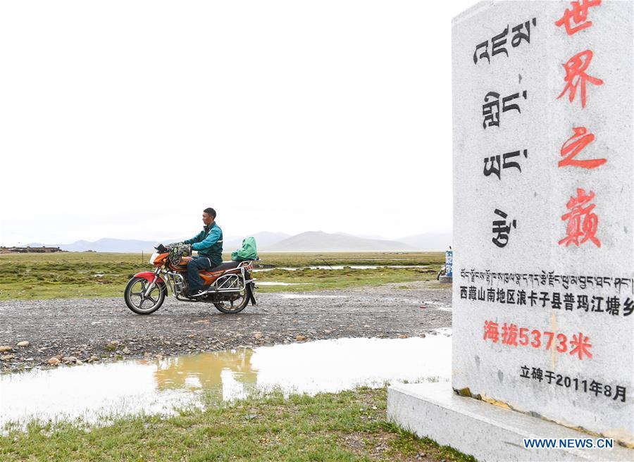 Motorbike courier Gesang Cering performs a mail delivery task in Pumaqangtang Township of Nagarze County in Shannan, southwest China\'s Tibet Autonomous Region, July 23, 2018. In Pumaqantang Township, the highest township in China, working as a postal service staff means delivering mails to addresses at altitudes of 5,000 meters and above. Gesang Cering, 29, is a motorbike courier with the local township branch of China Post. Twice a week, Gesang calls on the plateau villages under the township on a 160-km route, coping with extreme oxygen and temperature conditions. Despite its harsh geography, Tibet Autonomous Region has substantially improved the local postal service over the four decades since China\'s reform and opening up. By the end of 2017, the postal road network had managed to cover all towns and counties within the autonomous region. (Xinhua/Li He)