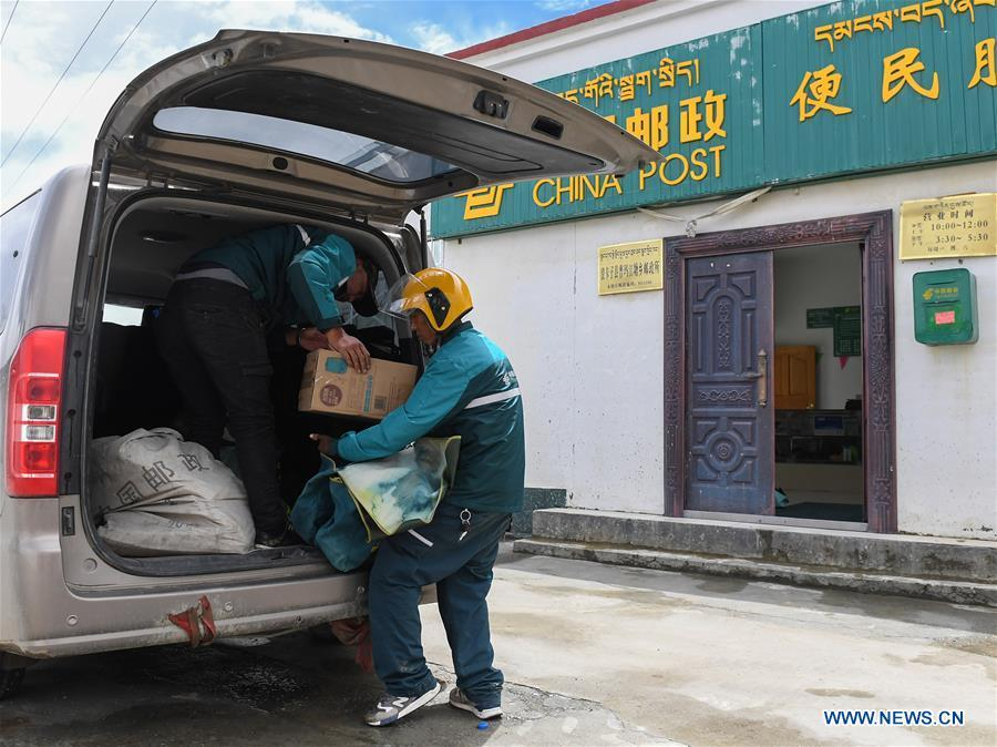 Motorbike courier Gesang Cering (R) and a workmate unload postal packages at the township branch of China Post in Pumaqangtang Township of Nagarze County in Shannan, southwest China\'s Tibet Autonomous Region, July 27, 2018. In Pumaqantang Township, the highest township in China, working as a postal service staff means delivering mails to addresses at altitudes of 5,000 meters and above. Gesang Cering, 29, is a motorbike courier with the local township branch of China Post. Twice a week, Gesang calls on the plateau villages under the township on a 160-km route, coping with extreme oxygen and temperature conditions. Despite its harsh geography, Tibet Autonomous Region has substantially improved the local postal service over the four decades since China\'s reform and opening up. By the end of 2017, the postal road network had managed to cover all towns and counties within the autonomous region. (Xinhua/Li He)