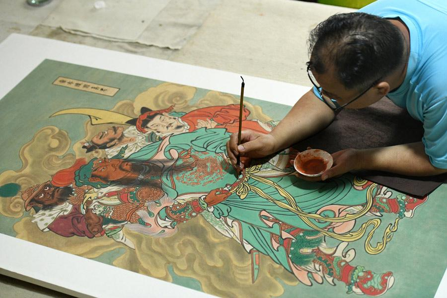 Yao Shulong makes a replica of a traditional Chinese New Year painting of Pilu Temple in his studio on July 24, 2018.  (Photo/Xinhua)