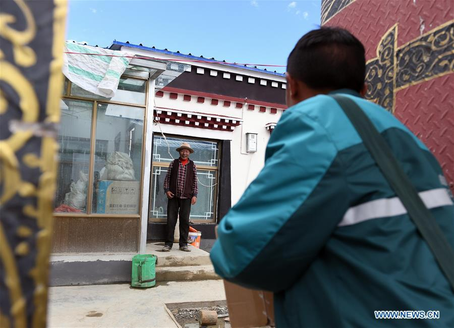 Motorbike courier Gesang Cering delivers a mail package to a client in Pumaqangtang Township of Nagarze County in Shannan, southwest China\'s Tibet Autonomous Region, July 27, 2018. In Pumaqantang Township, the highest township in China, working as a postal service staff means delivering mails to addresses at altitudes of 5,000 meters and above. Gesang Cering, 29, is a motorbike courier with the local township branch of China Post. Twice a week, Gesang calls on the plateau villages under the township on a 160-km route, coping with extreme oxygen and temperature conditions. Despite its harsh geography, Tibet Autonomous Region has substantially improved the local postal service over the four decades since China\'s reform and opening up. By the end of 2017, the postal road network had managed to cover all towns and counties within the autonomous region. (Xinhua/Li He)