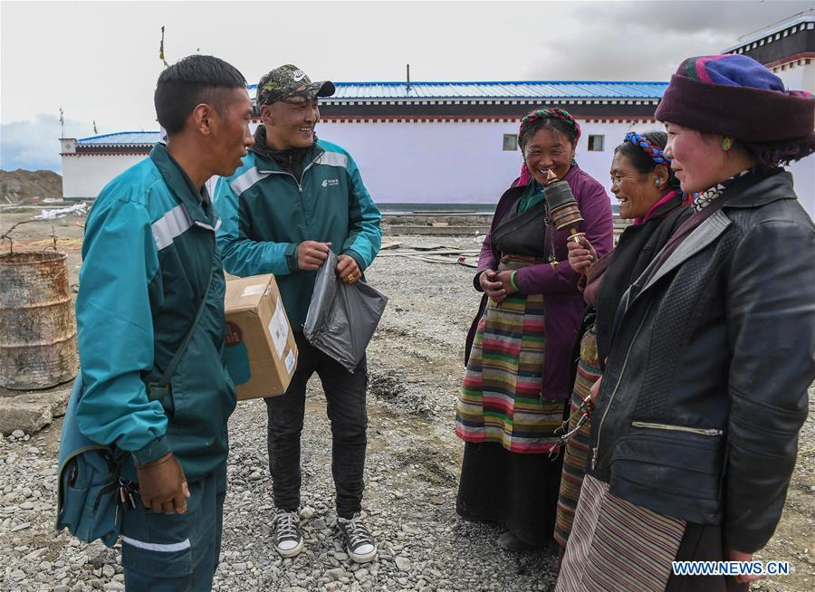 Motorbike courier Gesang Cering (1st L) and his workmate Cering Quba (2nd L) talk with clients in Pumaqangtang Township of Nagarze County in Shannan, southwest China\'s Tibet Autonomous Region, July 27, 2018. In Pumaqantang Township, the highest township in China, working as a postal service staff means delivering mails to addresses at altitudes of 5,000 meters and above. Gesang Cering, 29, is a motorbike courier with the local township branch of China Post. Twice a week, Gesang calls on the plateau villages under the township on a 160-km route, coping with extreme oxygen and temperature conditions. Despite its harsh geography, Tibet Autonomous Region has substantially improved the local postal service over the four decades since China\'s reform and opening up. By the end of 2017, the postal road network had managed to cover all towns and counties within the autonomous region. (Xinhua/Li He)