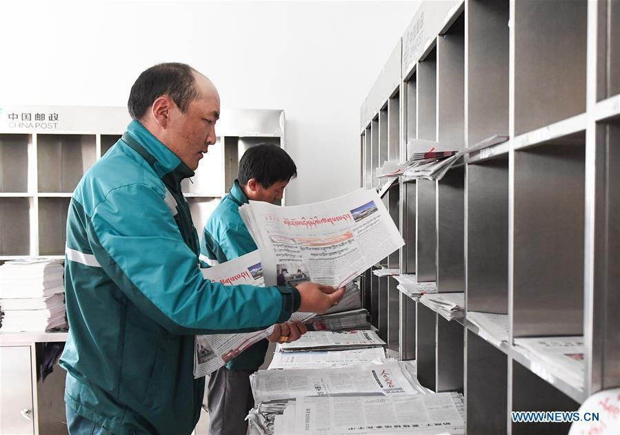 Postal courier Cering Quba sorts newspapers at the county branch of China Post in Nagarze County in Shannan, southwest China\'s Tibet Autonomous Region, July 23, 2018. In Pumaqantang Township, the highest township in China, working as a postal service staff means delivering mails to addresses at altitudes of 5,000 meters and above. Gesang Cering, 29, is a motorbike courier with the local township branch of China Post. Twice a week, Gesang calls on the plateau villages under the township on a 160-km route, coping with extreme oxygen and temperature conditions. Despite its harsh geography, Tibet Autonomous Region has substantially improved the local postal service over the four decades since China\'s reform and opening up. By the end of 2017, the postal road network had managed to cover all towns and counties within the autonomous region. (Xinhua/Li He)