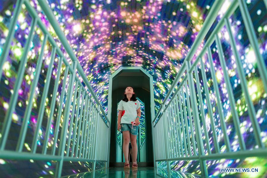 A girl walks through a corridor in Inner Mongolia Science and Technology Museum in Hohhot, north China\'s Inner Mongolia Autonomous Region, July 27, 2018. Children take part in various classes and activities to enrich their summer vacation life. (Xinhua/Ding Genhou)