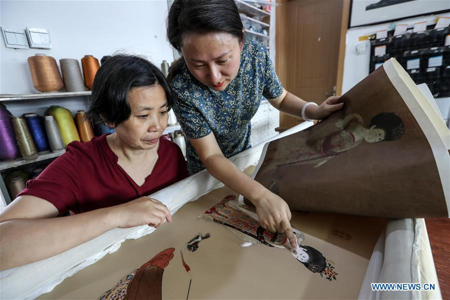 Wang Qin (R) and embroidery worker Lu Xuezhen compare embroidery and painting works in east China\'s Jiangsu Province, July 25, 2018. An exhibition displaying Wang Qin\'s collections and creations of Suzhou embroidery version of classic Chinese painting works concluded in Suzhou on Sunday. (Xinhua/Yang Lei)