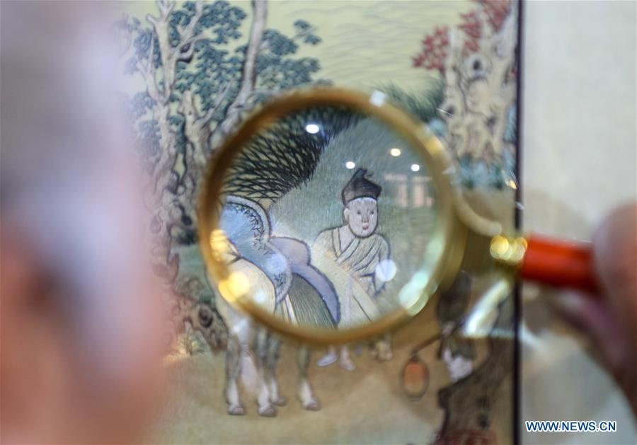 A visitor views a Suzhou embroidery exhibit during an exhibition in Suzhou, east China\'s Jiangsu Province, July 29, 2018. The exhibition displayed Wang Qin\'s collections and creations of Suzhou embroidery version of classic Chinese painting works. (Xinhu