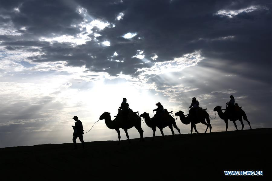 Tourists ride camels at the Mingsha Mountain and Crescent Spring scenic spot in Dunhuang, northwest China\'s Gansu Province, July 29, 2018. (Xinhua/Zhang Xiaoliang)