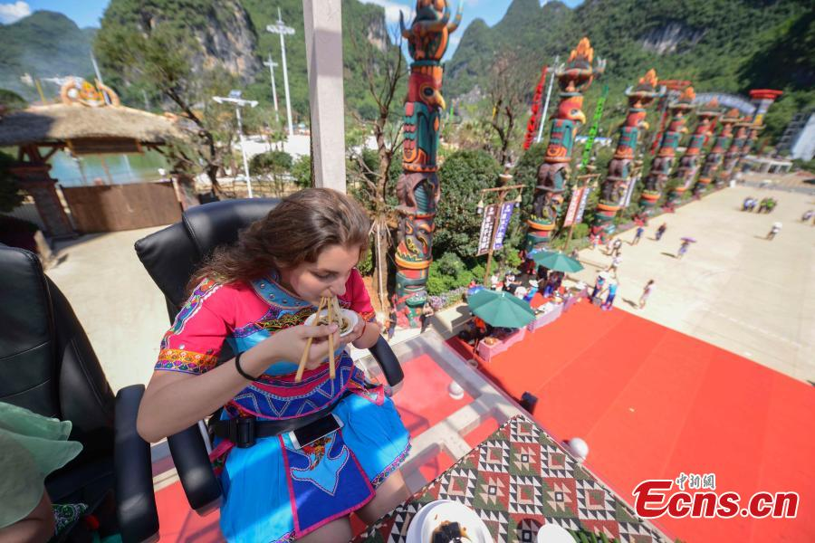 A Ukrainian woman takes a rice noodle-eating challenge in a transparent room, hoisted 50 meters off the ground, near a giant statue at a scenic spot in Guilin City, South China's Guangxi Zhuang Autonomous Region, July 29, 2018. Scared of the height, the participants gave up on the dare when the room was just ten meters off the ground. (Photo: China News Service/Chen Chen)