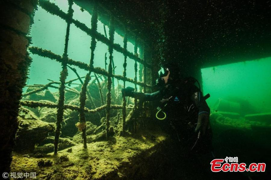 A diver explores Estonia's Rummu Prison, situated in the middle of a submerged quarry. When Estonia regained its independence in 1991, the Soviets moved out and the labor prison at Rummu was closed. This once eerie place to hold inmates is now an amazingly popular beach where people swim in the deep blue water and dive. (Photo/VCG)