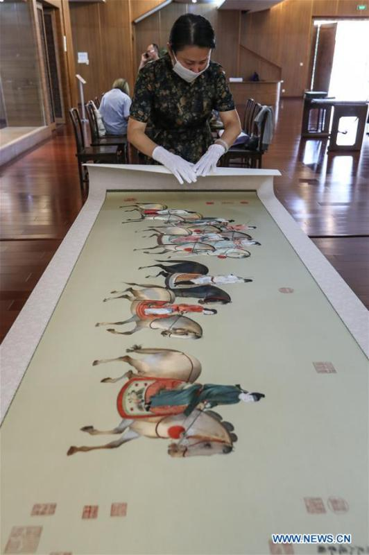 Wang Qin arranges Suzhou embroidery exhibits after an exhibition in Suzhou, east China\'s Jiangsu Province, July 29, 2018. An exhibition displaying Wang Qin\'s collections and creations of Suzhou embroidery version of classic Chinese painting works concluded in Suzhou on Sunday. (Xinhua/Yang Lei)