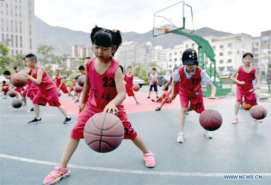 Children practice basketball in front of a gym in Longnan City, northwest China\'s Gansu Province, July 28, 2018. Children take part in various classes and activities to enrich their summer vacation life. (Xinhua/Ran Chuangchang)