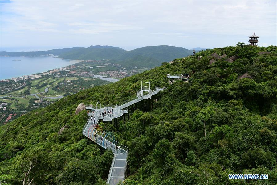 People visit a glass plank road built at the Yalong Bay forest park in Sanya, south China\'s Hainan Province, July 29, 2018. The 400-meter-long plank road will open for tourists in August. (Xinhua/Sha Xiaofeng)