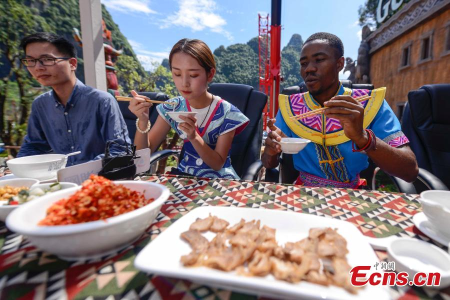 Participants face the challenge of eating rice noodles in a transparent room, hoisted 50 meters off the ground, near a giant statue at a scenic spot in Guilin City, South China's Guangxi Zhuang Autonomous Region, July 29, 2018. Scared of the height, the participants gave up on the dare when the room was just ten meters off the ground. (Photo: China News Service/Chen Chen)