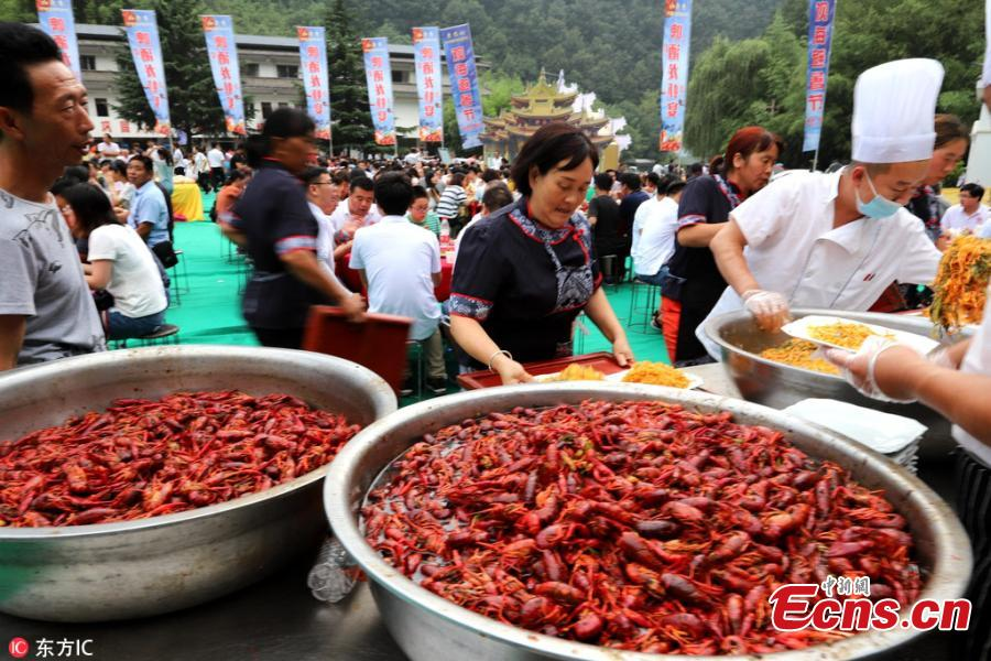 A crayfish banquet is held on Laojun Mountain in Luoyang City, Central China's Henan Province, July 28, 2018. Organizers prepared more than 1,000 kilograms of crayfish and another 1,000 kilograms of fruit, as well as providing beer, to entertain thousands of visitors, who quickly gobbled up the treats. (Photo/IC)