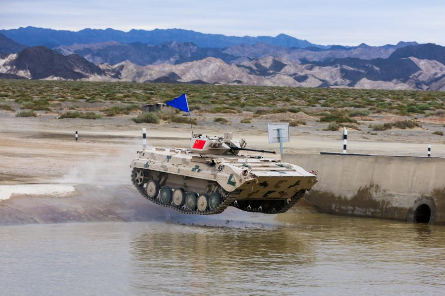 An infantry fighting vehicle (right) of the People\'s Liberation Army participates in the Suvorov Attack race during the International Army Games 2018 in Korla, Xinjiang Uygur autonomous region on Monday.(Photo/China Daily)