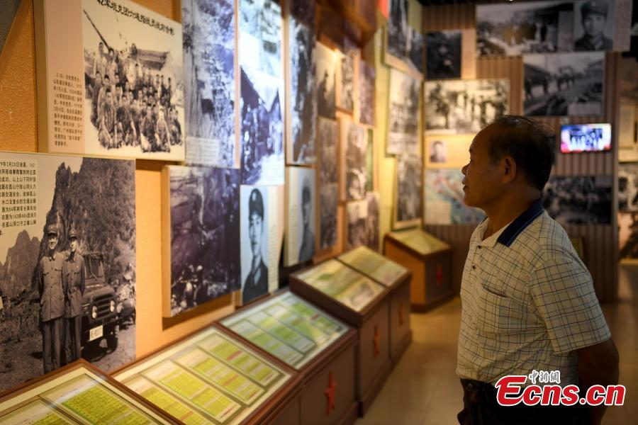 Niu Bentong looks at photos depicting the China-Vietnam war in Longzhou County, South China's Guangxi Zhuang Autonomous Region, July 30, 2018. Niu participated in the China-Vietnam war and witnessed the death of many of his comrades-in-arms in front of him. In 1980, Niu chose to work in the cemetery, where 1,902 martyrs lie, and he continued to work there for 37 years until his retirement this year. He has helped correct information related to more than 400 martyrs and has also shared details online. In his spare time, Niu continues to help at the cemetery, saying it's hard to forget the days of life and death spent alongside his fellow soldiers. (Photo: China News Service/Yu Jing)