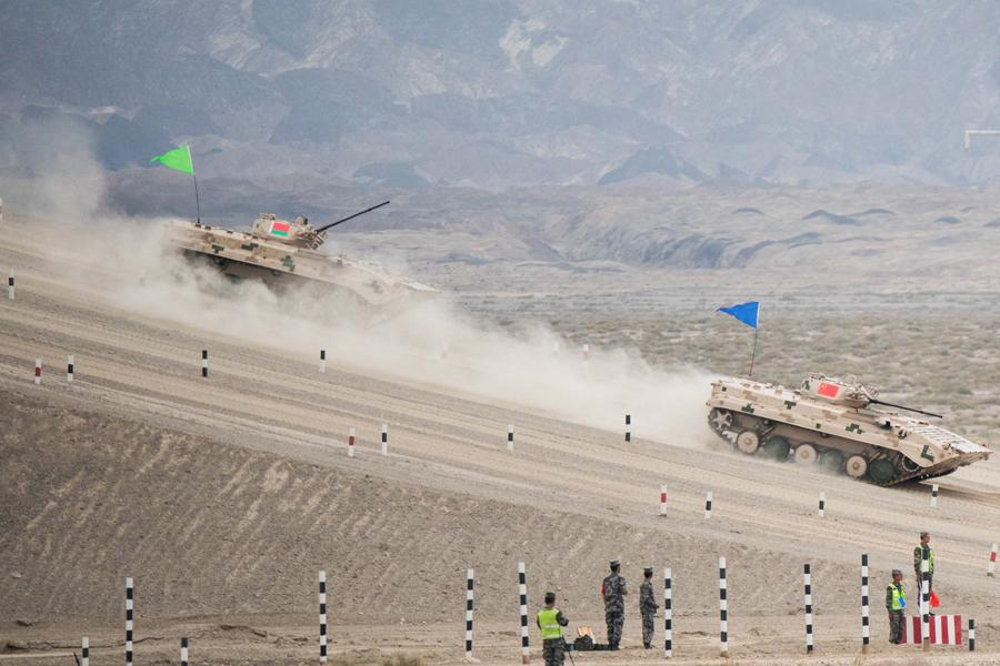 An infantry fighting vehicle (right) of the People\'s Liberation Army participates in the Suvorov Attack race during the International Army Games 2018 in Korla, Xinjiang Uygur autonomous region on Monday. XU KANGPING/FOR CHINA DAILY  