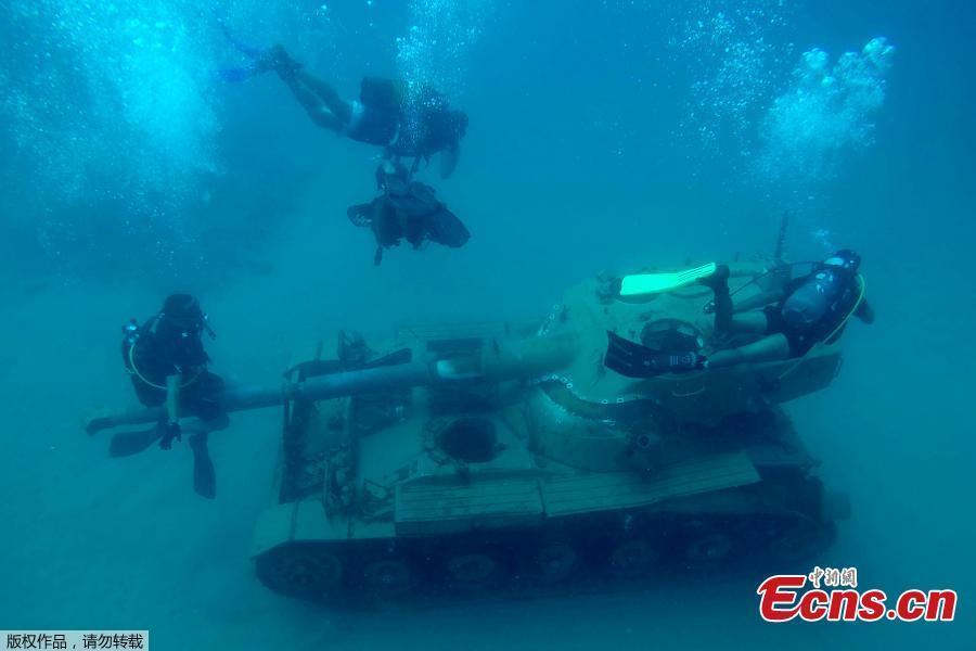 Divers swim around immersed tanks off the coast of Sidon, Lebanon, July 28, 2018. Lebanese environmentalists sank 10 old tanks and other armored vehicles to the bottom of the Mediterranean Sea in a novel attempt to attract divers and create new habitats for marine life. (Photo/Agencies)