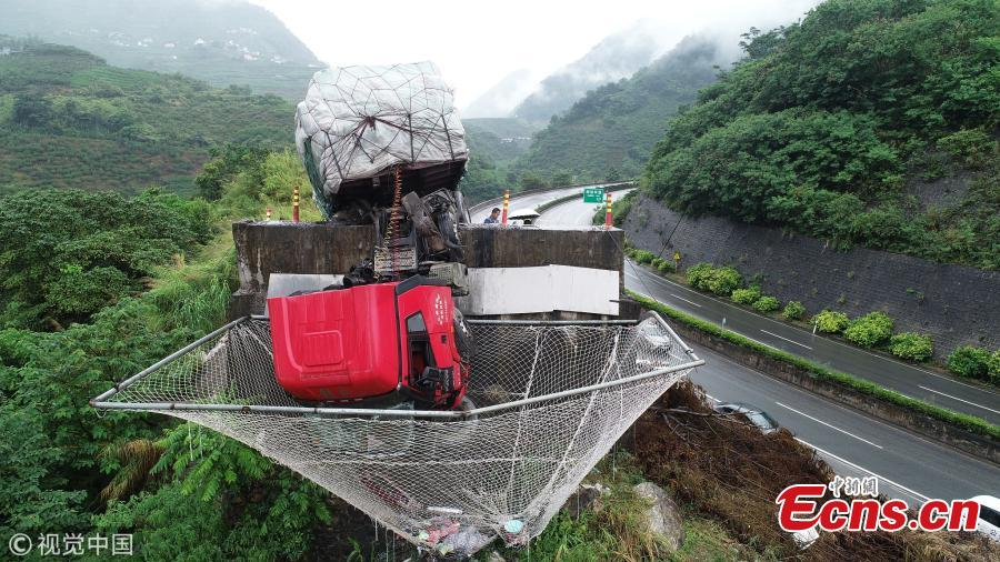 A cargo truck's cabin hangs on a slip road in Yuxi City, Southwest China's Yunnan Province, July 26, 2018. Having lost control of the truck on a 27-kilometer-long downward slope, known as the \