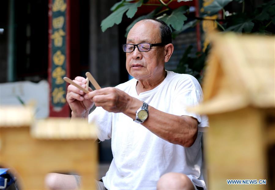 Zhang Xiaocheng makes a model using discarded wooden sticks in Chengguan Town of Wu\'an City, north China\'s Hebei Province, July 31, 2018. 70-year-old Zhang has made over 60 handicrafts using discarded wooden sticks. (Xinhua/Wang Xiao)