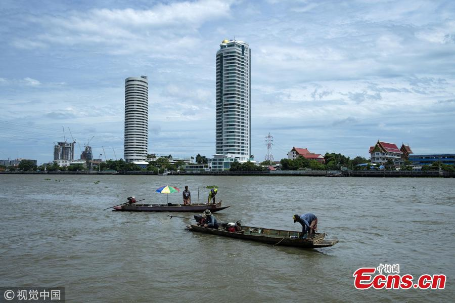 This picture taken on June 12, 2018 shows divers working from their boats as they scour the bottom of Bangkok\'s Chao Phraya river for valuables. There is a small community in Thailand known as \'Indiana Jones\' divers, who brave the inky-black underworld of the trash-filled waterway in search of coins, china, jewelry and scrap metal. (Photo/VCG)