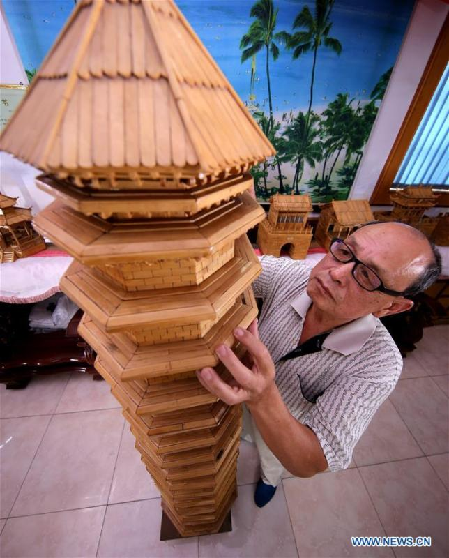 Zhang Xiaocheng checks a model of ancient building made of discarded wooden sticks in Chengguan Town of Wu\'an City, north China\'s Hebei Province, July 31, 2018. 70-year-old Zhang has made over 60 handicrafts using discarded wooden sticks. (Xinhua/Wang Xiao)