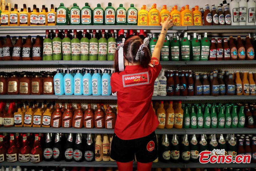 British artist Lucy Sparrow, 32, adjusts bottles of alcohol on shelves in her art installation supermarket in which everything is made of felt, in Los Angeles, California, U.S. July 31, 2018. (Photo/Agencies)
