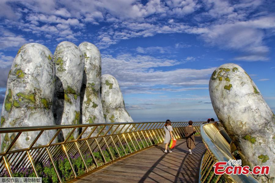 In this photograph taken on July 31, 2018, visitors walk along the 150-meter long Cau Vang \'Golden Bridge\' in the Ba Na Hills near Danang. Nestled in the forested hills of central Vietnam two giant concrete hands emerge from the trees, holding up a glimmering golden bridge crowded with gleeful visitors taking selfies at the country\'s latest eccentric tourist draw. Suspended 1400 meters above sea level, the bridge combines eight sections and stretches 150 meters long. (Photo/VCG)