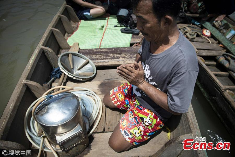 This picture taken on June 12, 2018 shows diver Bhoomin Samang praying in front of his homemade metal scuba helmet before he dives to the bottom of the Bangkok\'s Chao Phraya river to search for valuables. There is a small community in Thailand known as \'Indiana Jones\' divers, who brave the inky-black underworld of the trash-filled waterway in search of coins, china, jewelry and scrap metal. (Photo/VCG)