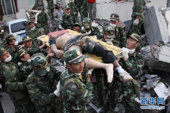 PLA soldiers carry a wounded man after an earthquake in Wenchuan county, Sichuan Province, May 15, 2008. (Photo/Xinhua)