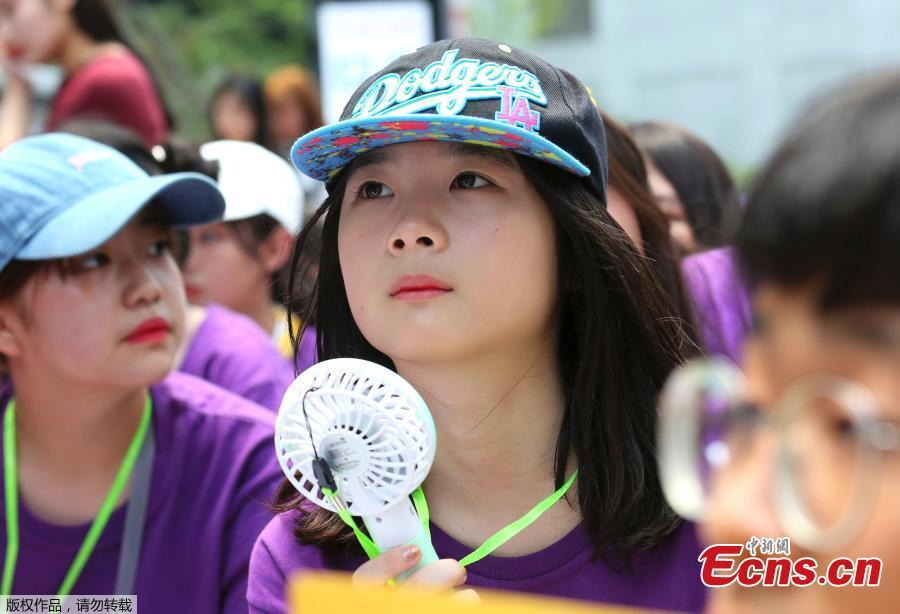 Middle school students use portable fans amid the sweltering heat during a rally demanding full compensation and apology for wartime sex slaves from Japanese government in front of the Japanese embassy in Seoul, South Korea, Aug. 1, 2018. South Korean Meteorological Administration issued a heat wave warning for Seoul and other cities. (Photo/Agencies)