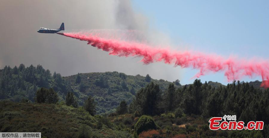 An aircraft drops fire retardant to slow the spread of the Carr Fire, west of Redding, California, U.S. July 27, 2018. A 70-year-old woman and her two great-grandchildren were among six people killed when a wildfire engulfed entire communities in northern California, officials and family members said. (Photo/Agencies)