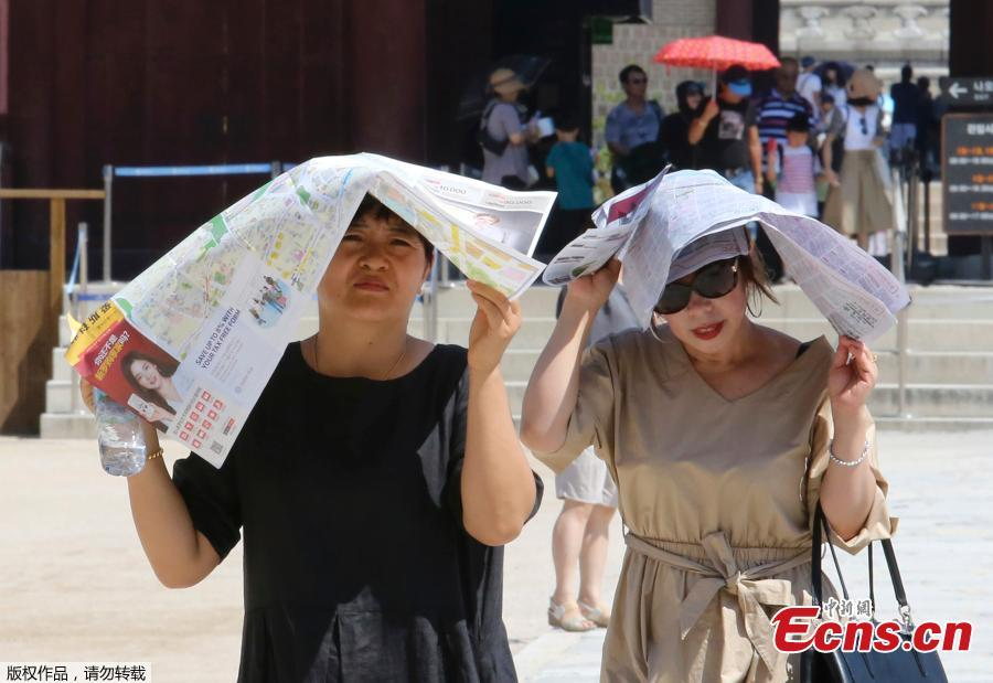 Women use papers to avoid sunshine at the Gyeongbok Palace, the main royal palace during the Joseon Dynasty, in Seoul, South Korea, Aug. 1, 2018. South Korean Meteorological Administration issued a heat wave warning for Seoul and other cities. Seoul logged its highest-ever temperature of 38.8 C on Wednesday since 1907. (Photo/Agencies)