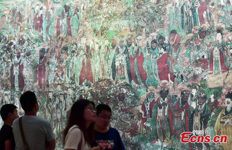 Visitors look at an exhibition of murals at the Hebei Museum in Shijiazhuang City, Hebei Province, Aug. 2, 2018. The murals date back to the Ming Dynasty (1368-1644) and were from the Pilu Temple. They are known for their great composition, superb craftsmanship and rich connotation. (Photo: China News Service/Zhai Yujia)