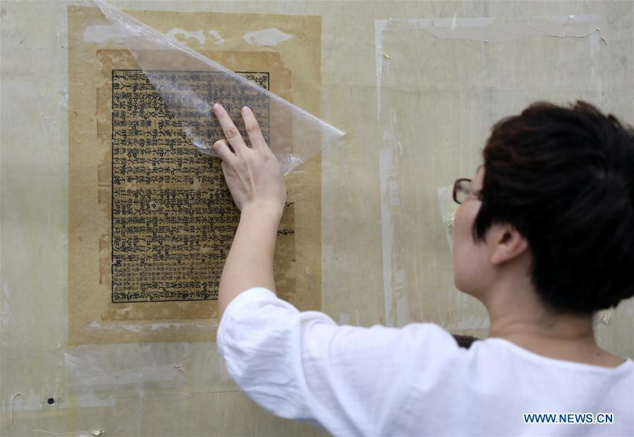 Gao Huiyun restores an ancient book at a workshop in Shijiazhuang, capital of north China\'s Hebei Province, Aug. 2, 2018. Gao Huiyun is a teacher of cultural relics restoration and protection at Hebei Vocational Art College. Gao has restored over 1,000 ancient books in her 13-year career time. (Xinhua/Chen Qibao)