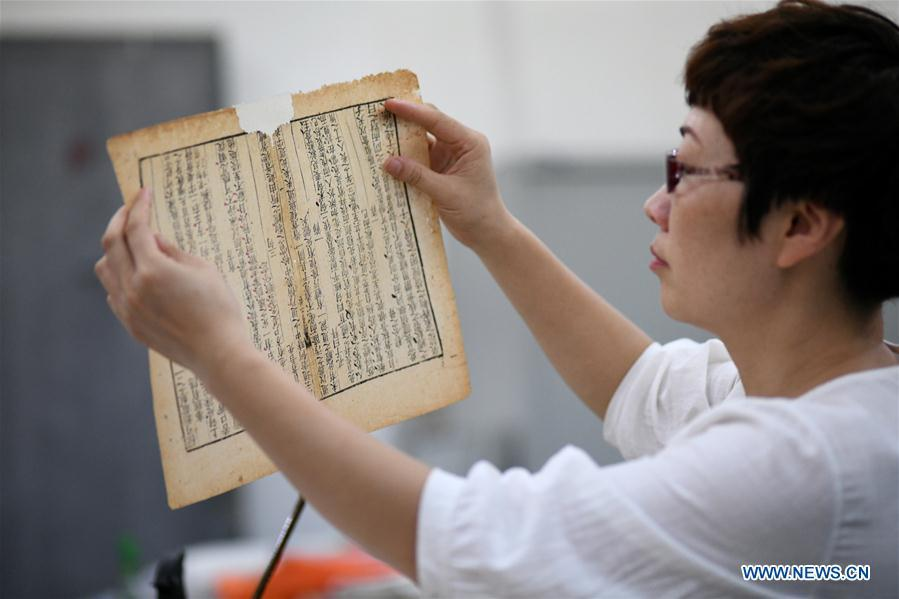 Gao Huiyun checks an ancient book at a workshop in Shijiazhuang, capital of north China\'s Hebei Province, Aug. 2, 2018. Gao Huiyun is a teacher of cultural relics restoration and protection at Hebei Vocational Art College. Gao has restored over 1,000 ancient books in her 13-year career time. (Xinhua/Chen Qibao)