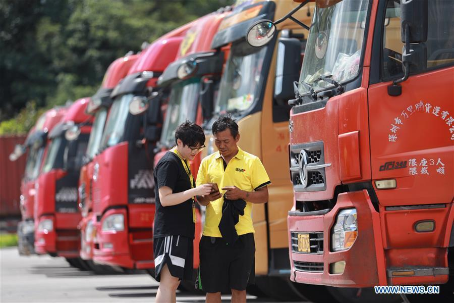A staff member helps truck driver Li Haijun (R) use the Truck Alliance app, China\'s Uber-type service for trucks, with smartphone in Guiyang, capital of southwest China\'s Guizhou Province, Aug. 1, 2018. Guizhou has become a pioneer in China\'s big data development. Big data is being widely applied in government management, business and daily life, contributing over 20 percent to the economic growth of Guizhou Province. The number of big data-related companies in Guizhou Province has grown from less than 1,000 in 2013 to more than 8,500 in 2018. (Xinhua/Liu Xu)